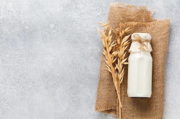 Domowe dietetyczne mleko roślinne z płatków owsianych na szaro. pojęcie zdrowej diety. skopiuj miejsca i baner.