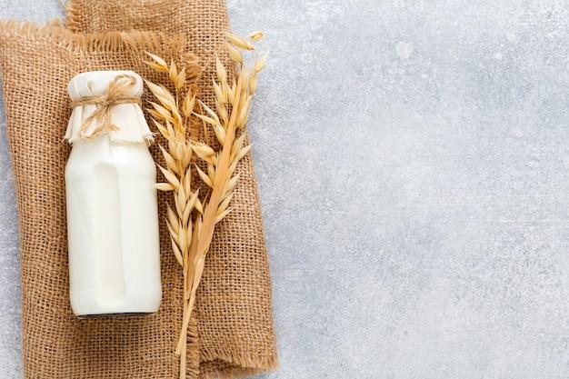 Domowe dietetyczne mleko roślinne z płatków owsianych na szarym tle. dieta zdrowa i zdrowa koncepcja żywności. skopiuj miejsce. widok z góry.