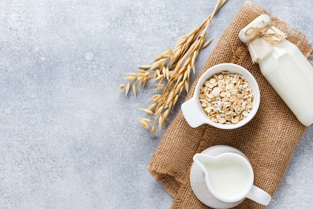 Domowe dietetyczne mleko roślinne z płatków owsianych na szarym tle. pojęcie zdrowej diety. skopiuj miejsce i widok banner.top.