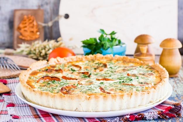 Domowe francuskie ciasto quiche z pomidorem, serem i ziołami na talerzu