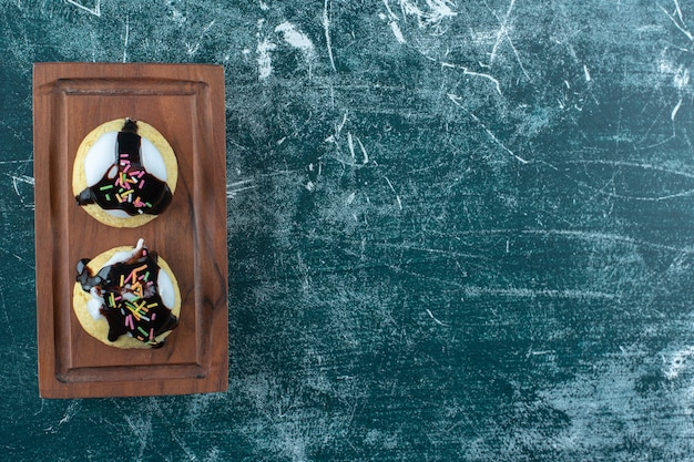 Domowe glazurowane ciasteczka na drewnianym talerzu, na niebieskiej powierzchni