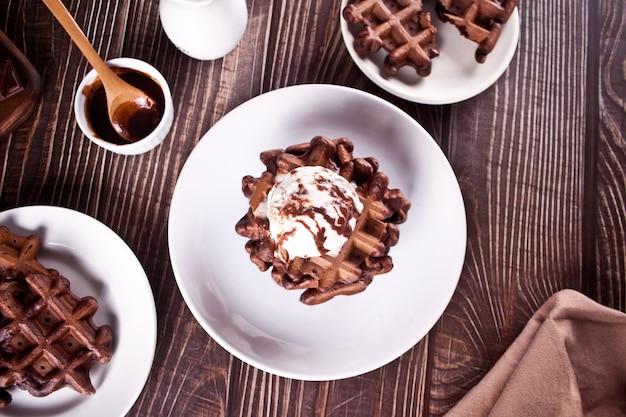 Domowe gofry czekoladowe z lodami dekorowanymi syropem czekoladowym.
