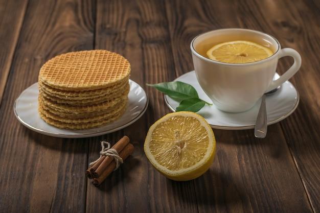 Domowe gofry i herbata z cynamonem i cytryną na drewnianym stole. domowe ciasta z herbatą.