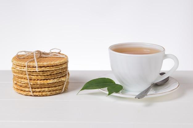 Domowe gofry i świeża herbata na białym stole na jasnym tle. domowe ciasta z herbatą.