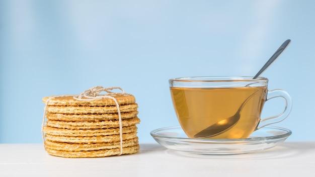 Domowe gofry z herbatą na białym stole na niebieskim tle. domowe ciasta z herbatą.