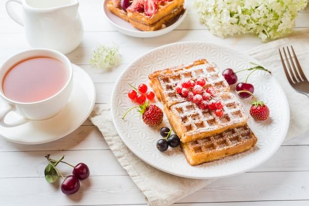 Domowe gofry z letnich jagód na talerzu. filiżanka herbaty na lekkim stole. selektywne ustawianie ostrości.