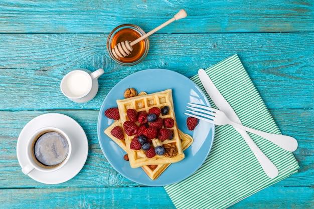 Domowe gofry z malinami i jagodami, filiżanka kawy, mleko i sztućce