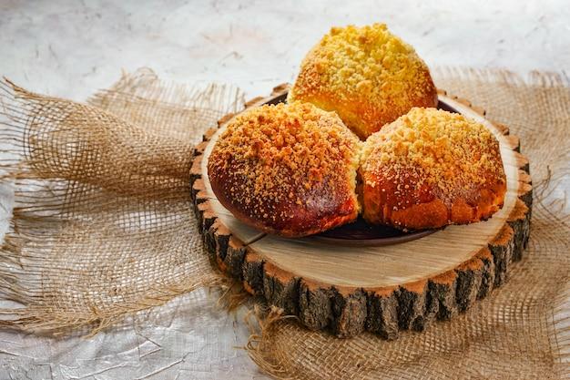 Domowe gorące bułeczki pieczone na drewnianej płycie. ekologiczne czyste jedzenie, rustykalne tradycyjne śniadanie. słodkie wypieki z cukrem. puste miejsce na tekst, kopia przestrzeń. zdjęcie wysokiej jakości