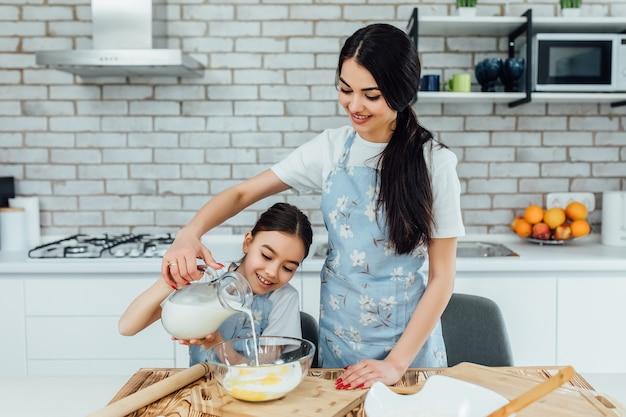 Domowe gotowanie dla twojej duszy. mała dziewczynka i jej siostra przygotowuje domowe jedzenie. cudowni kucharze gotują pyszne domowe potrawy. styl życia