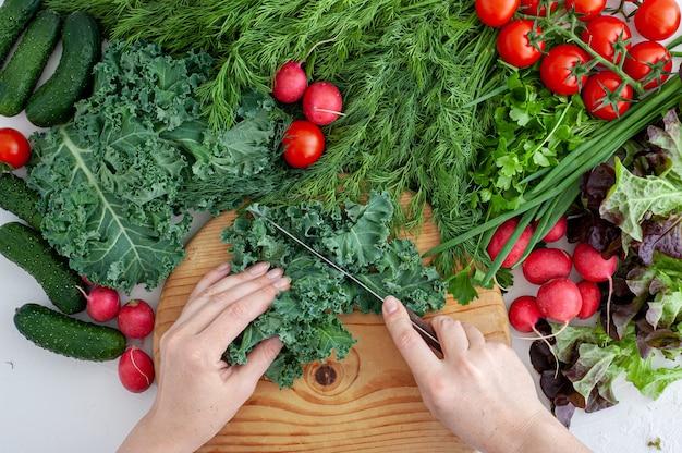 Domowe gotowanie proces gotowania zdrowego wegańskiego jedzenia kobiece dłonie ścinają trawę na drewnianej desce na t...