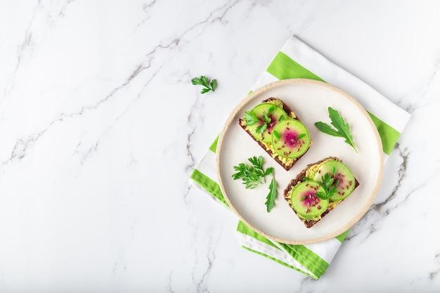 Domowe grzanki z organicznym awokado z rzodkwi arbuzowej i nasionami flex na białym marmurowym tle