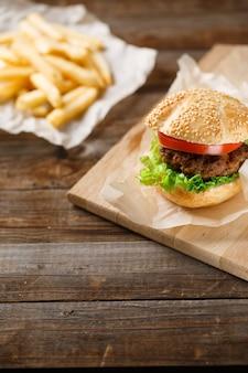 Domowe hamburgery i frytki na drewnianym stole