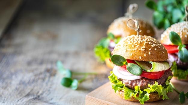 Domowe hamburgery z kotletem, świeżą sałatą, pomidorami, cebulą na drewnianym stole. skopiuj miejsce