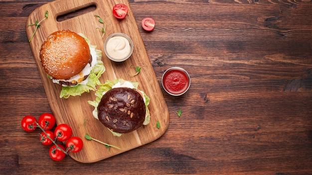 Domowe hamburgery z łososiem, pomidorami, sałatą i serem na desce do krojenia i zardzewiałym tle. widok z góry z miejscem na tekst.
