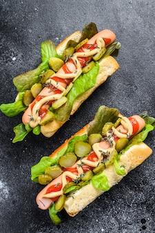 Domowe hot dogi z warzywami, sałatą i przyprawami.