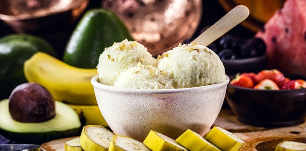 Domowe i wegańskie lody bananowe bez mleka w plastikowej misce z recyklingu, z owocami na powierzchni