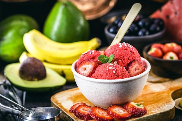 Domowe i wegańskie lody truskawkowe bez mleka, z owocami w tle