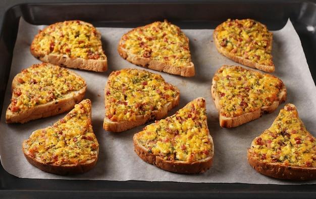 Domowe kanapki na ciepło z serem i kiełbasą, na pergaminie na blasze do pieczenia, format poziomy, zbliżenie