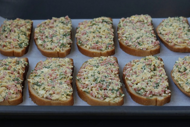 Domowe kanapki z serem i kiełbasą przed pieczeniem na pergaminie na blasze do pieczenia, proces gotowania, orientacja pozioma