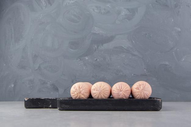 Domowe kiełbaski gotowane na czarnej tablicy.