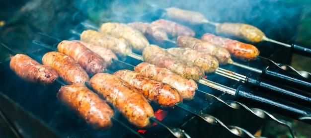 Domowe kiełbaski z grilla na świeżym powietrzu. smaczne jedzenie na imprezę grillową.