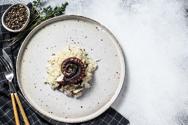 Domowe klasyczne risotto z mackami ośmiornicy. białe szare tło. widok z góry. skopiuj miejsce