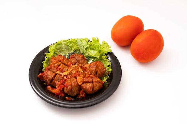 Domowe klopsiki z sosem pomidorowym i przyprawami podawane na czarnym talerzu na białym tle