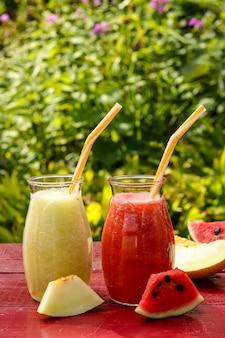 Domowe koktajle owocowe z arbuza i melona na stole w ogrodzie,