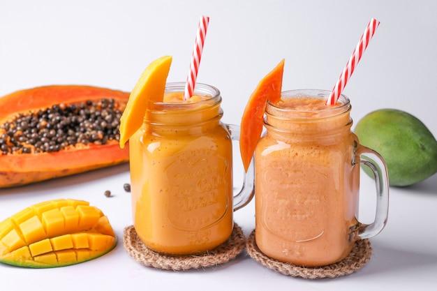 Domowe koktajle z owoców tropikalnych z papai i mango na białej powierzchni, orientacja pozioma