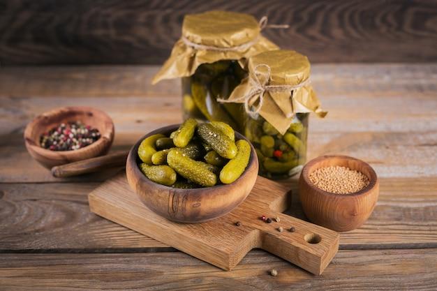 Domowe konserwy. marynowane ogórki korniszony z koperkiem i czosnkiem w szklanym słoju na drewnianym stole. sałatki warzywne na zimę.