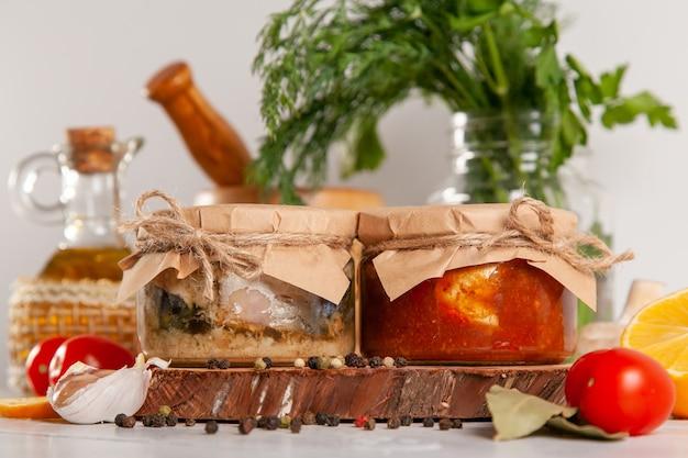 Domowe konserwy rybne z makreli w oleju i paście pomidorowej. szklane słoiki z rybami w puszkach.