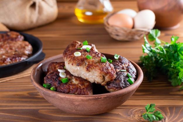 Domowe kotlety wołowe pieczone w ceramicznej misce na drewnianym stole, świeża pietruszka