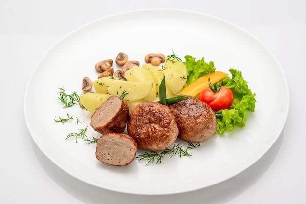 Domowe kotlety z ziemniakami i warzywami na białym tle.