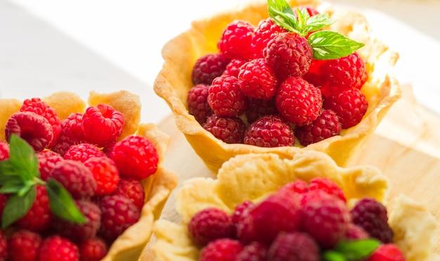 Domowe kruche ciasto malinowe. letnie tartaletki z jagodami z kremem waniliowym i listkami mięty. świeże desery na na białym tle. wolne miejsce na kopię.