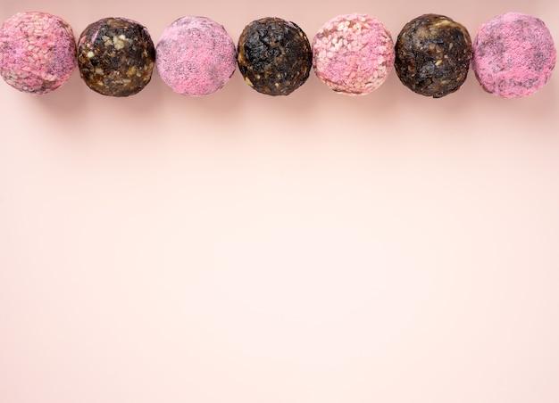 Domowe kulki energetyczne z różowego smoczego owocu matcha widok z góry zdrowe słodycze z orzechów i suszonych śliwek daktylowych