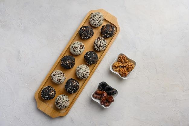 Domowe kulki zdrowej energii z owoców, orzechów, kakao, miodu z bliska na drewnianej tacy