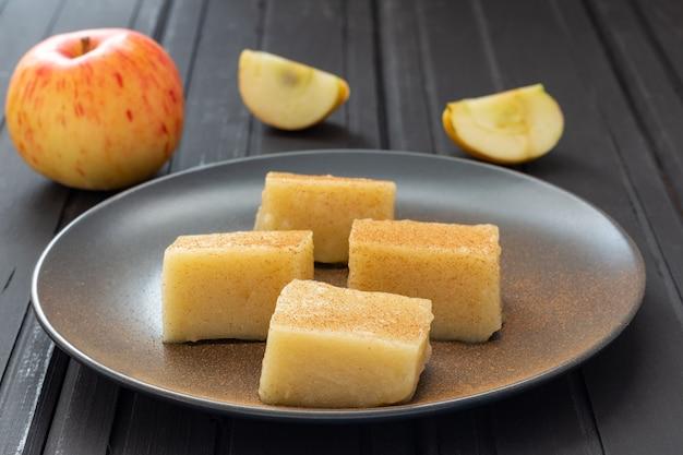 Domowe kwadraty galaretki jabłkowej z cynamonem na czarnym talerzu