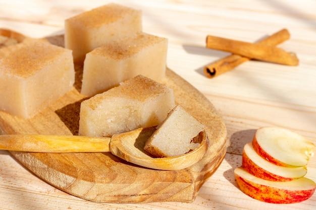 Domowe kwadraty galaretki jabłkowej z cynamonem na drewnianym stole.