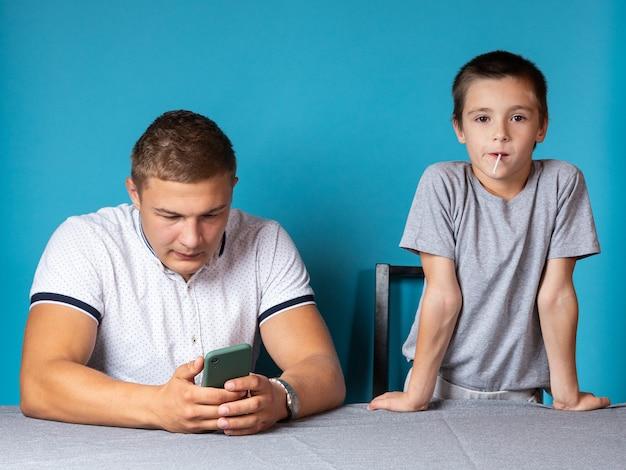 Domowe lekcje z dzieckiem, tata jest rozpraszany przez telefon, podczas gdy syn jest znudzony i czeka na jego uwagę