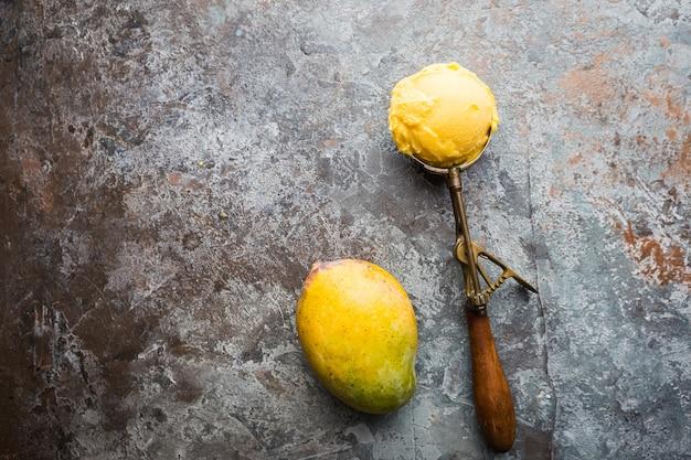 Domowe lody mango w miseczkach ze świeżymi owocami w kolorze ciemnoszarym