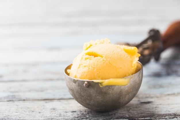Domowe lody mango w miskach ze świeżymi owocami na białym drewnianym