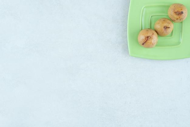 Domowe marynowane owoce na zielonym talerzu.