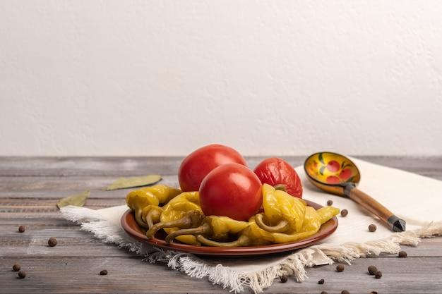 Domowe marynowane papryki i pomidory na ceramicznym talerzu na lnianej serwetce. obok tradycyjnej rosyjskiej drewnianej łyżki. styl rustykalny. skopiuj miejsce