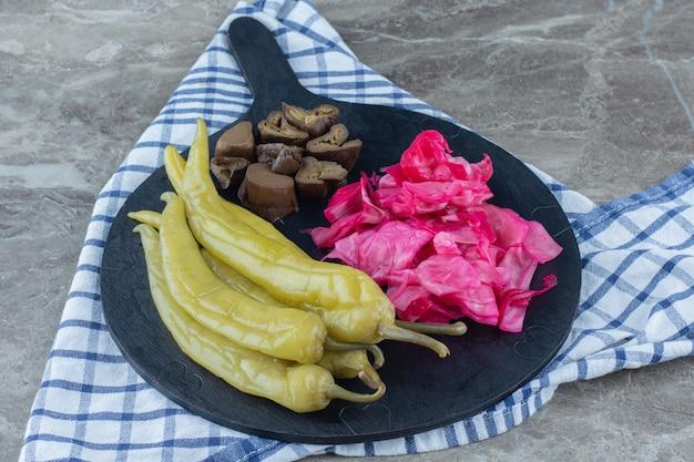 Domowe marynowane warzywa na drewnianej desce do krojenia