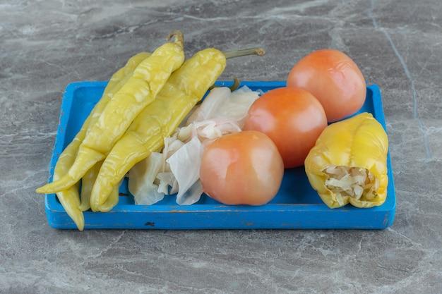Domowe marynowane warzywa na drewnianym talerzu