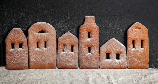Domowe miasteczko z piernika stojącego w rzędzie posypane cukrem pudrem na czarnym tle.