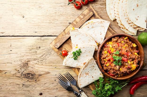 Domowe mięso wołowe meksykańskie fajitas z papryką, kukurydzą i tortillą na drewnianej powierzchni, widok z góry