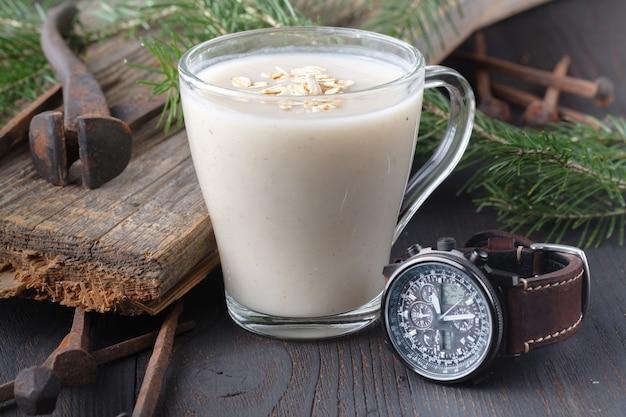 Domowe mleko owsiane, zegarek na rękę i gałązka