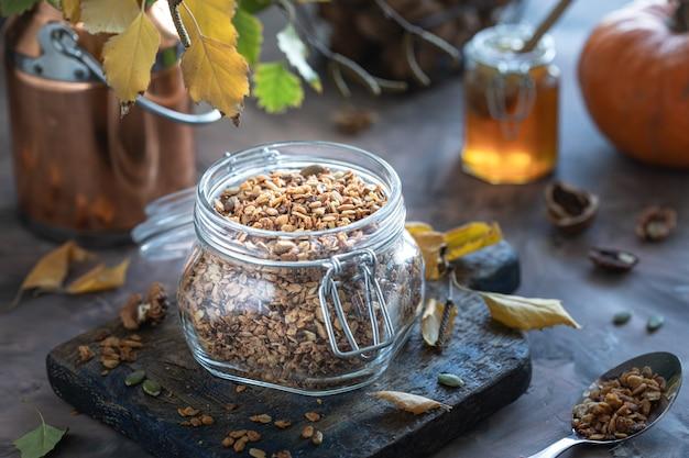 Domowe musli dyniowe z orzechami i ziarnami w szklanym słoju na zdrowe śniadanie. jesienne martwa natura