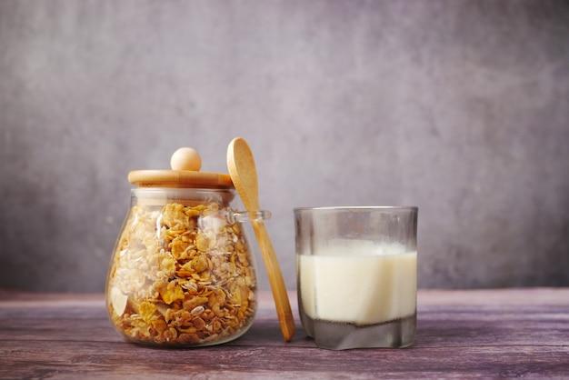 Domowe musli w misce i szklanka mleka na czarno